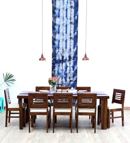 addfc8bb18 Acropolis cushioned 8 seater dining table set is a bold and seamless  creation crafted from Sheesham wood. This dining set is simply a treat to  an eye.